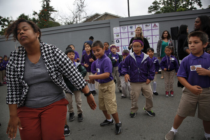 Students and teachers at Fuerza Community Prep dance during their daily morning assembly.