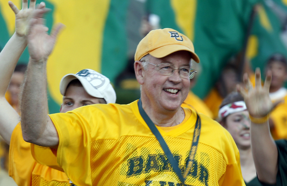 Baylor University President Kenneth Starr runs onto the football field before a 2011 game against Texas Christian University in Waco, Texas. Starr became president of Baylor in 2010. (LM Otero/AP)