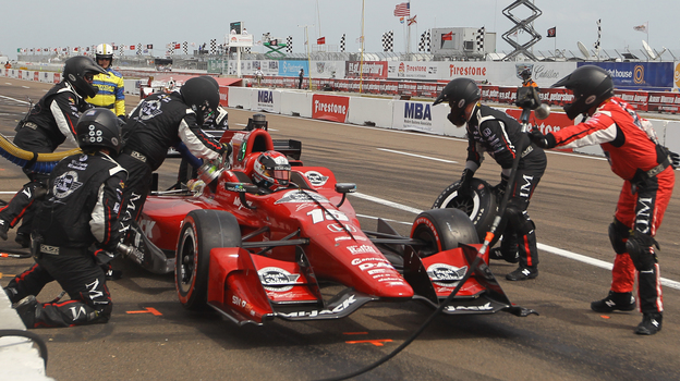 Crew chief Donny Stewart, far right, throws his air gun back towards the wall at the end of a pit stop at the Firestone Grand Prix of St. Petersburg, Fla. (AP)