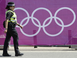 A British police officer walks in front the Olympic rings logo in Coventry, England, in July 2012.