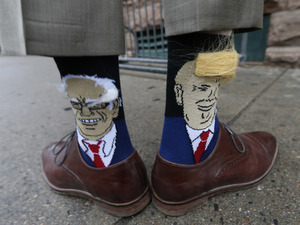 Colorado Gov. John Hickenlooper shows off his socks--one with Democratic presidential candidate Bernie Sanders and the other with Republican candidate Donald Trump--before entering his former brewpub for a book signing event to mark the release of his autobiography.