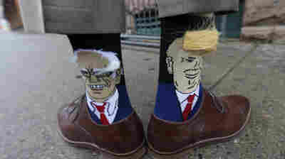 Colorado Gov. John Hickenlooper, a Democrat, shows off his socks — one with Democratic presidential candidate Bernie Sanders and the other with Republican candidate Donald Trump.