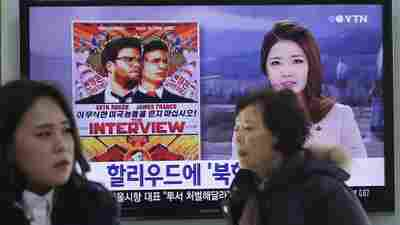 """People walk past a TV screen showing a poster of Sony Picture's """"The Interview"""" in a news report, at the Seoul Railway Station in Seoul, South Korea. The FBI says North Korea hacked into Sony Pictures computer systems as retribution for the film."""