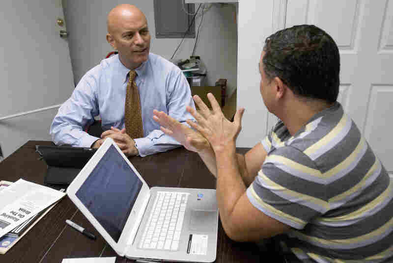 Tim Canova, left, talks with his chief of staff, Richard Bell at his campaign headquarters in Hollywood, Fla.