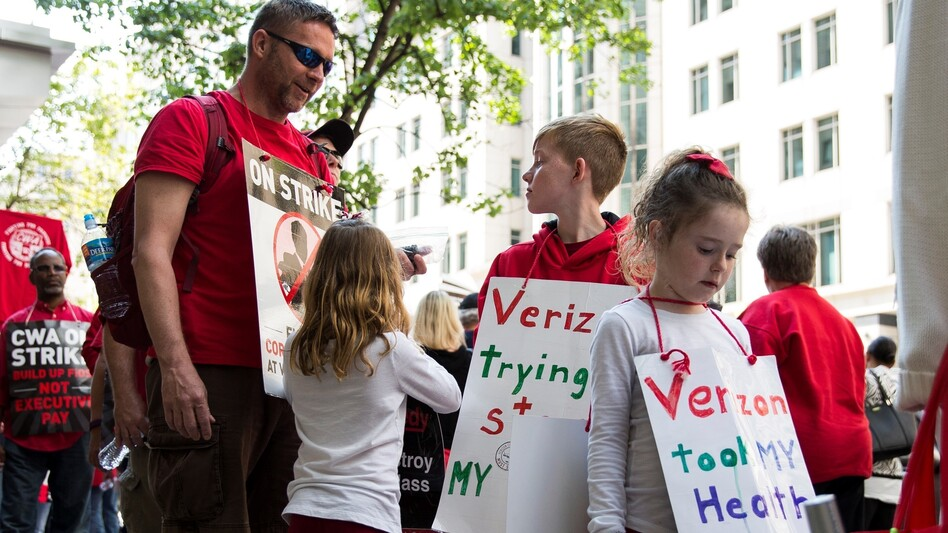 A Verizon worker on strike marches with his children and fellow employees on May 19. With no new contract, workers' health insurance expired at the end of April.