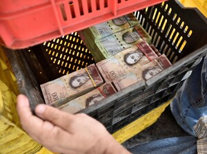 A man uses a vegetable container to carry currency notes in a market in Caracas on May 21. Amid a crushing economic crisis and triple-digit inflation, Venezuela's bolivar has lost so much value that the largest bill, the 100-bolivar note, is now worth less than a dime on the black market.