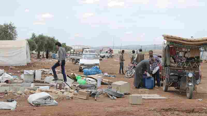 People gather their belongings Friday as they leave a refugee camp because of an Islamic State offensive near Azaz, Syria.