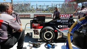 """Mark Bruce, left, looks on as others examine the car. Bruce is Graham Rahal's fueler, and he's had his share of close calls, like the time his fuel line broke open and ignited. """"Knock on wood, I've never been on fire,"""" he says."""