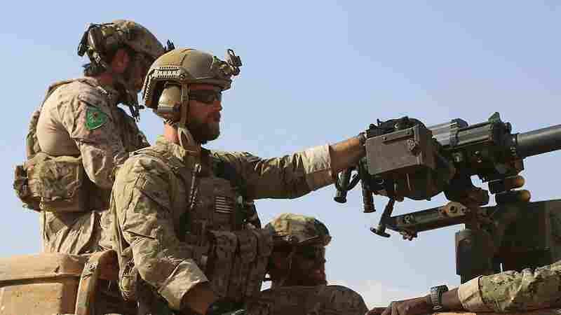 Armed men in uniform identified by Syrian Democratic forces as U.S. special operations forces ride in the back of a pickup truck in the village of Fatisah in the northern Syrian province of Raqqa on Wednesday.