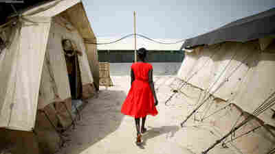 A woman walks between two of the tents that house the hospital wards. Most of the camp's residents are women and children.