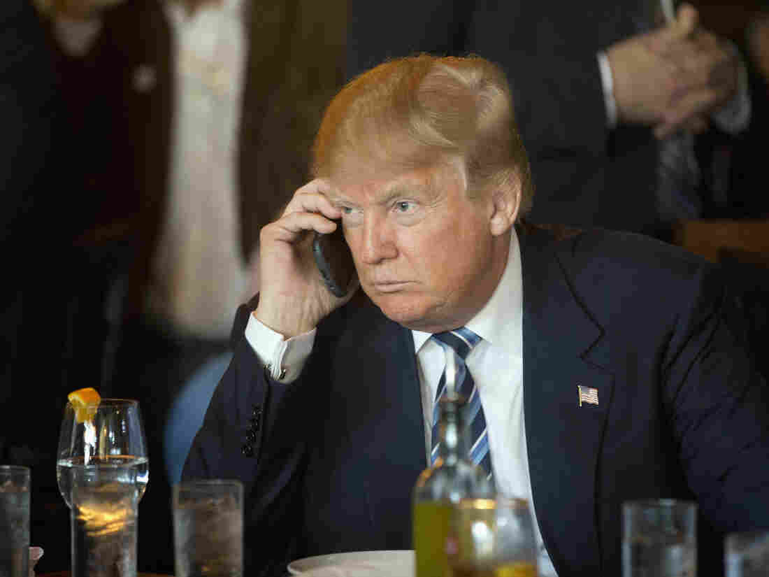 Republican presidential candidate Donald Trump listens to his mobile phone during a lunch stop, Thursday, Feb. 18, 2016, in North Charleston, S.C.