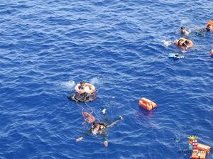Italian marines rescue migrants from the capsized boat.