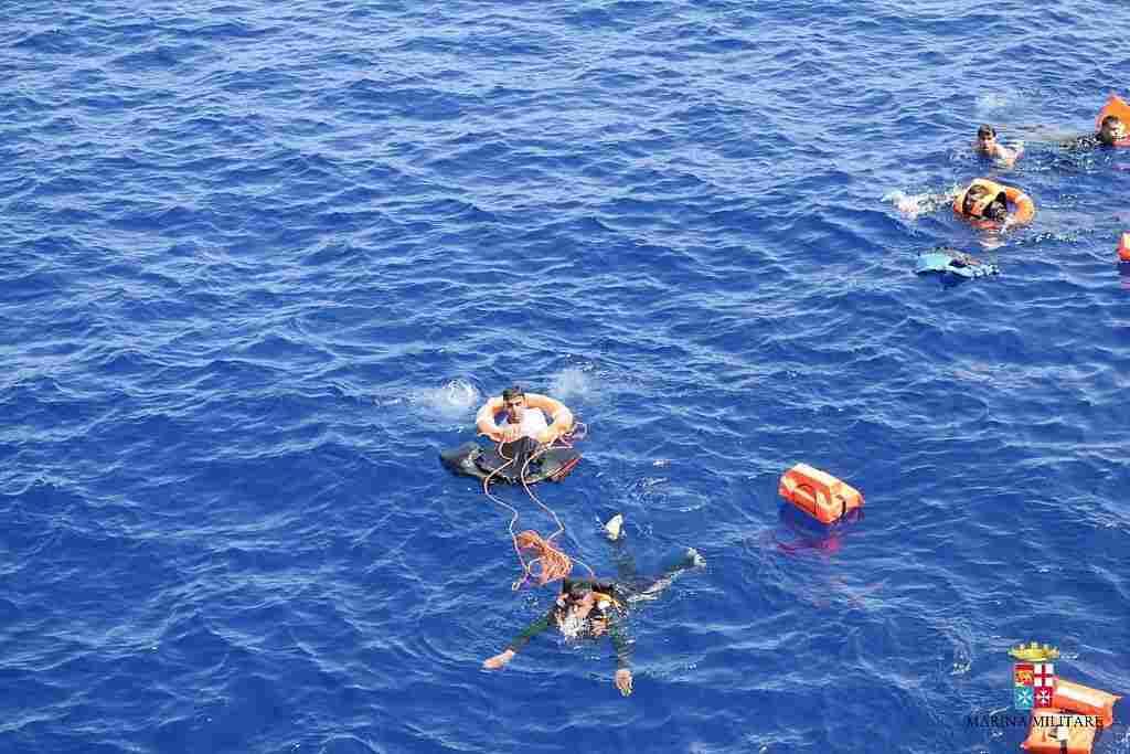 Italian marines rescue migrants from the capsized boat.