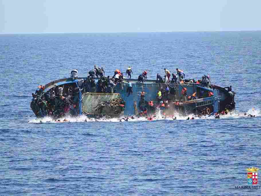 Migrants in an overcrowded boat, which was about to capsize, are rescued by Bettica and Bergamini ships of Italian Navy at Sicilian Strait, between Libya and Italy, in Mediterranean sea on Wednesday.