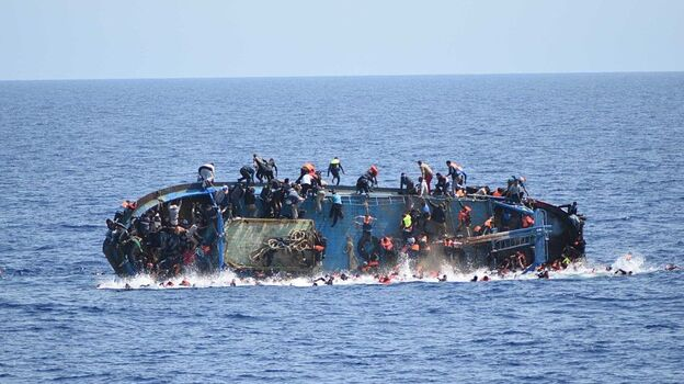 Migrants in an overcrowded boat, which was about to capsize, are rescued by Bettica and Bergamini ships of Italian Navy at Sicilian Strait, between Libya and Italy, in Mediterranean sea on Wednesday. (Getty Images)