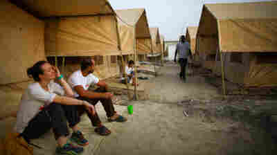 Morning at the MSF hospital compound in Bentiu, South Sudan. The two doctors, Jiske Steemsna (left) and Navpreet Sahsi, sit in front of the tents that serve as living quarters for the international workers during their three-to-six-month stints.