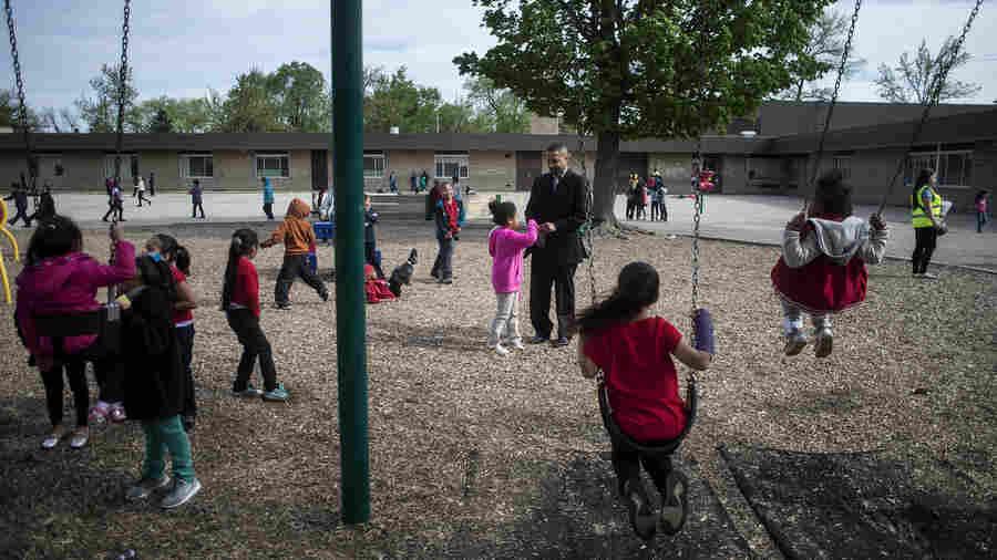 Mel Atkins (center) talks with a Buchanan Elementary School student during recess.