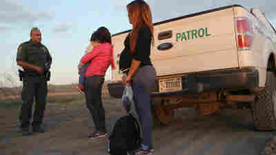 Immigrants from El Salvador, including one who says she is seven months pregnant, stand next to a U.S. Border Patrol truck after they turned themselves in to border agents on Dec. 7, 2015, near Rio Grande City, Texas.