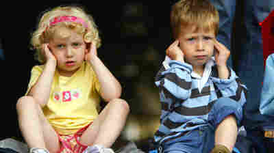Two very disappointed children cover their ears from what we can only assume is a relentless, unforgiving ear worm.