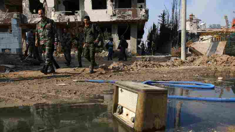 Syrian government forces patrol Daraya, a suburb of the capital, Damascus, on Feb. 24.
