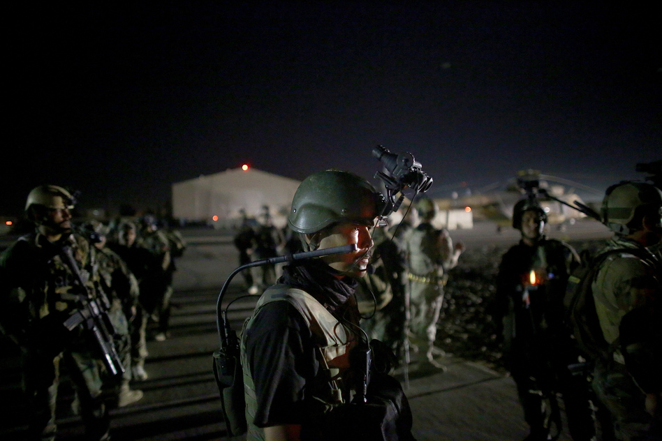 An Afghan commando stands on the tarmac, wearing night vision gear. The elite commandos are about to fly into an area controlled by Taliban fighters. Their mission: to sweep a village for Taliban fighters. (David Gilkey/NPR)