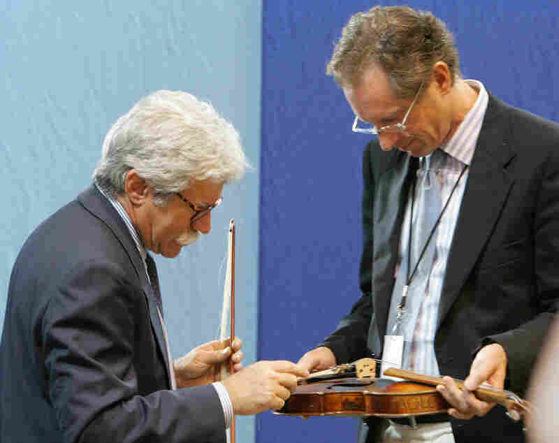 Appraisers Fred Oster, left, and David Bonsey, review a 1920 French violin at an Antiques Roadshow event in Los Angeles in 2005. Many stringed instruments throughout history have been made using small amounts of ivory.