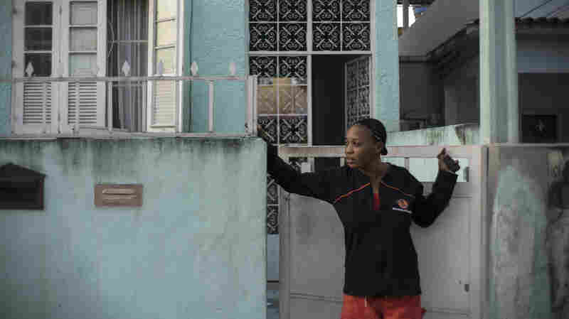 Yolande Mabika, a refugee and judo athlete from the Democratic Republic of Congo, stands outside her newly rented apartment in Rio de Janeiro. Mabika and fellow Congolese athlete Popole Misenga came to Brazil in 2013 to compete in a judo championship; they became refugees after their coach vanished with their passports and money.