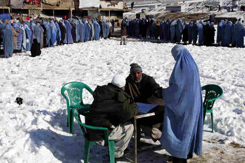An Afghan widow registers before receiving her rations at a CARE International food distribution center in Kabul, the capital of Afghanistan, on Jan. 25, 2006. CARE International rations out flour, salt and cooking oil to some 12,000 widows in Kabul each month.