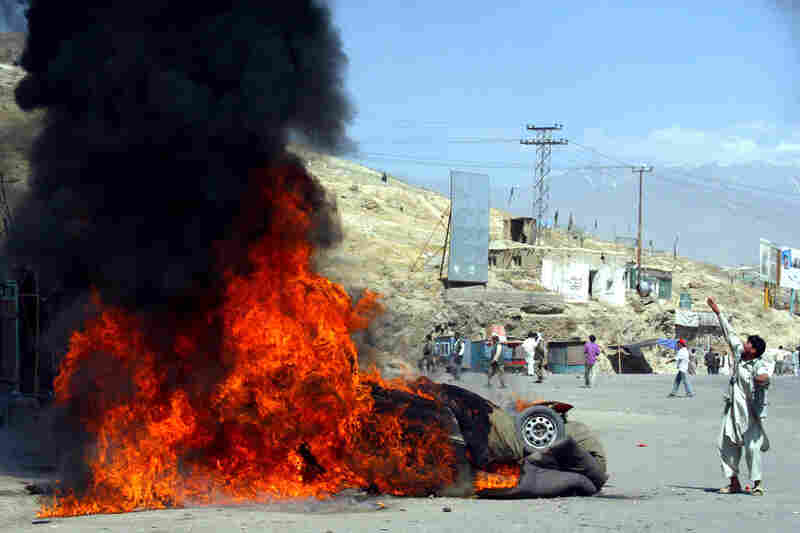 "An Afghan protester throws a stone at police near a burning police vehicle in Kabul, Afghanistan, on May 29, 2006. A deadly traffic accident involving U.S. troops sparked the worst riot in the Afghan capital since the fall of the Taliban regime, with hundreds of protesters looting shops and shouting ""Death to America!"" At least eight people were killed and 107 injured, an official said."