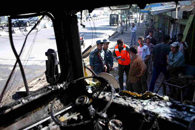 Afghan police officers inspect a bus destroyed in a bomb explosion in Kabul, Afghanistan, on July 5, 2006. Three bombs exploded in the Afghan capital in attacks that targeted buses carrying government workers and security forces, killing one bystander and injuring at least 47 other people, police and witnesses said.