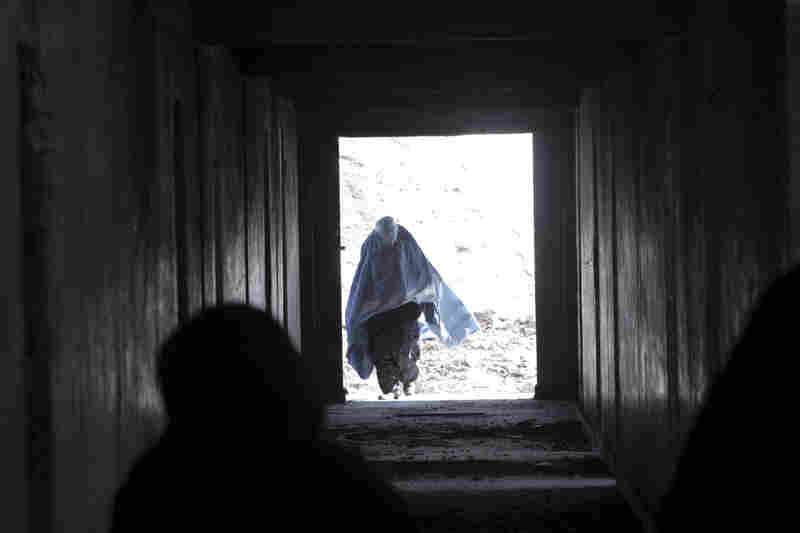 An Afghan woman walks in an abandoned building to receive food at a distribution center in Kabul, Afghanistan, on a winter day in January 2008.