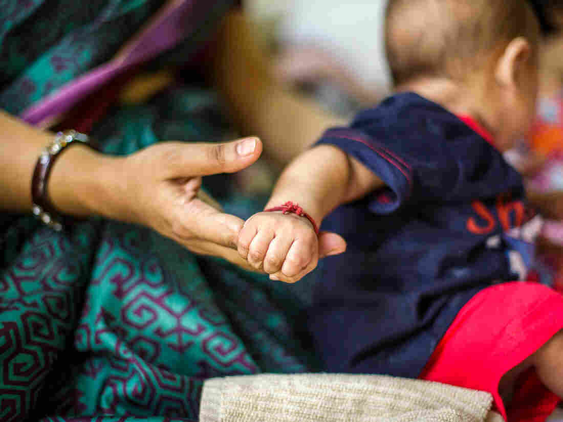 This picture depicts the strong bond between the mother and child. A five (5) to six (6) months old baby holds strongly on his mother's finger, even while his attention is elsewhere.