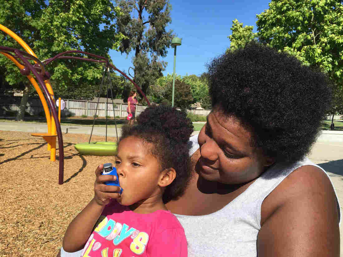 Zunika Crenshaw helps her 3-year-old daughter Jhase Crenshaw Bass with an asthma inhaler.