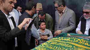 Ten-year-old Mustafa (center), son of Afghan reporter Zabihullah Tamanna, prays with relatives and friends next to the coffin during Tuesday's ceremony.