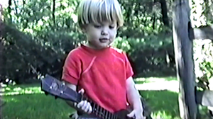 """A toddler plays a guitar in an old home movie clip featured in a new video for the Maybird song, """"Looking Back."""""""