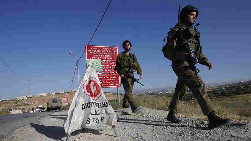 Israeli soldiers walk near a temporary checkpoint at the entrance of the Palestinian village of Yatta in the West Bank on Thursday after army forces entered the village in search of clues to Wednesday night's shootings in the Israeli city of Tel Aviv.