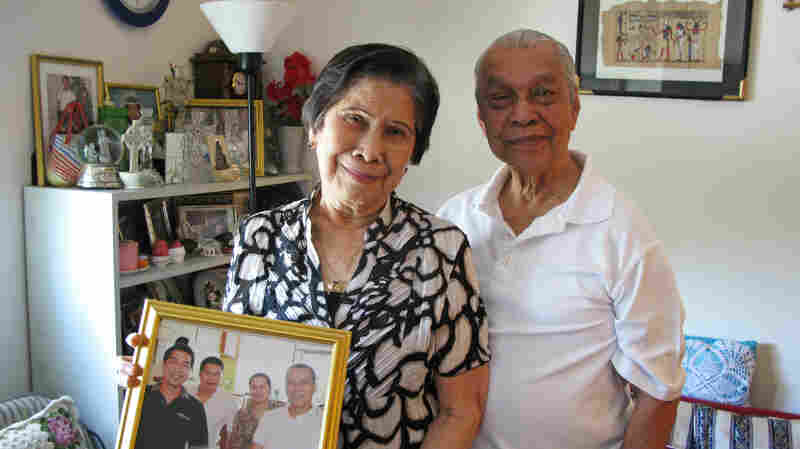 World War II veteran Rudolpho Panaglima lives in Arlington, Va., with his wife, Pura, who holds a portrait of their four children living abroad. Their eldest son, Rolando, has been waiting 20 years for a visa to move to the U.S. from the Philippines.