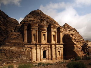 Sun peeks out of rain clouds to light up the famous monastery in Petra, Jordan.