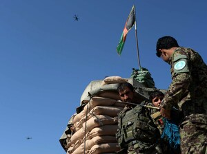 Afghan National Army soldiers stand guard as a U.S. helicopter flies over Jalalabad Airport on Oct. 2, 2015.