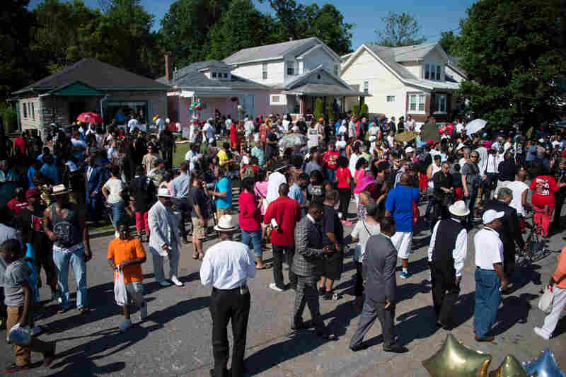 Hundreds gather outside boxing legend Muhammad Ali's childhood home, where mourners wait to pay their respects during a funeral procession in Louisville.