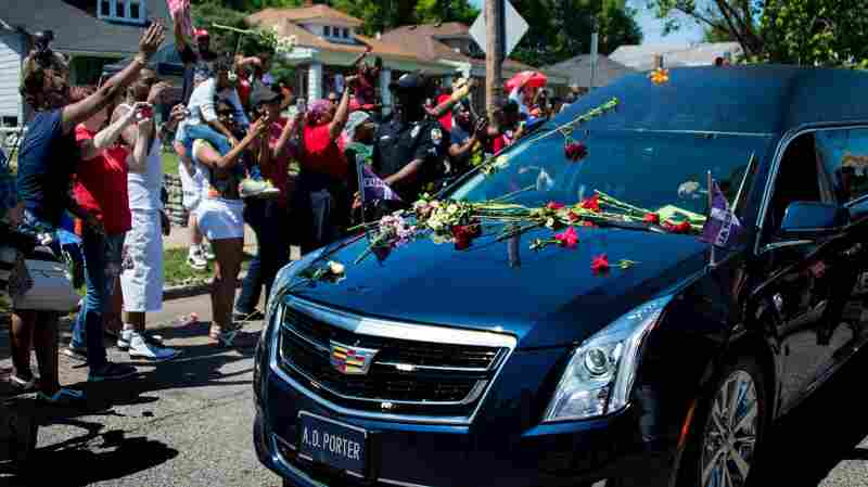 The hearse carrying boxing legend Muhammad Ali drives past his childhood home where mourners throw flowers as they pay their respects in Louisville, Ky.