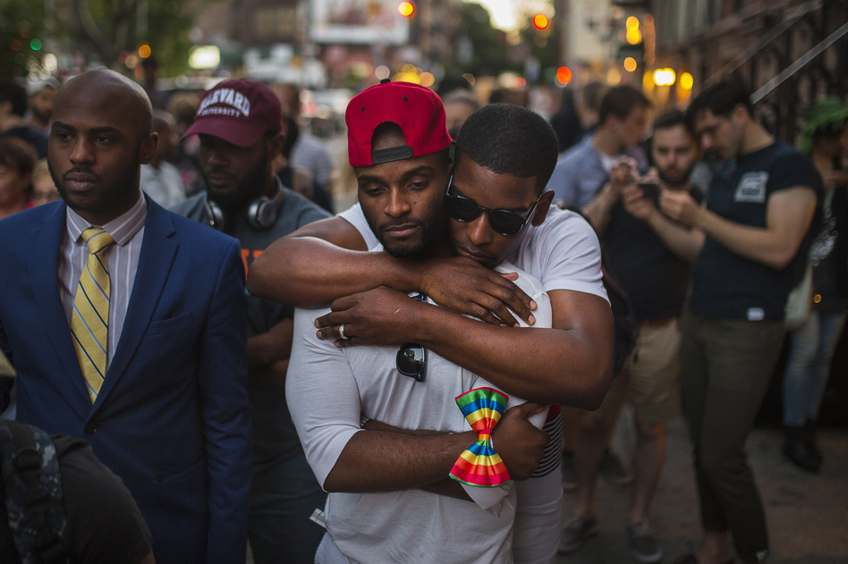 A couple hugs as people gather in front of a makeshift memorial in New York to remember the victims of the mass shooting in Orlando, Fla. on Sunday. (Andres Kudacki/AP)