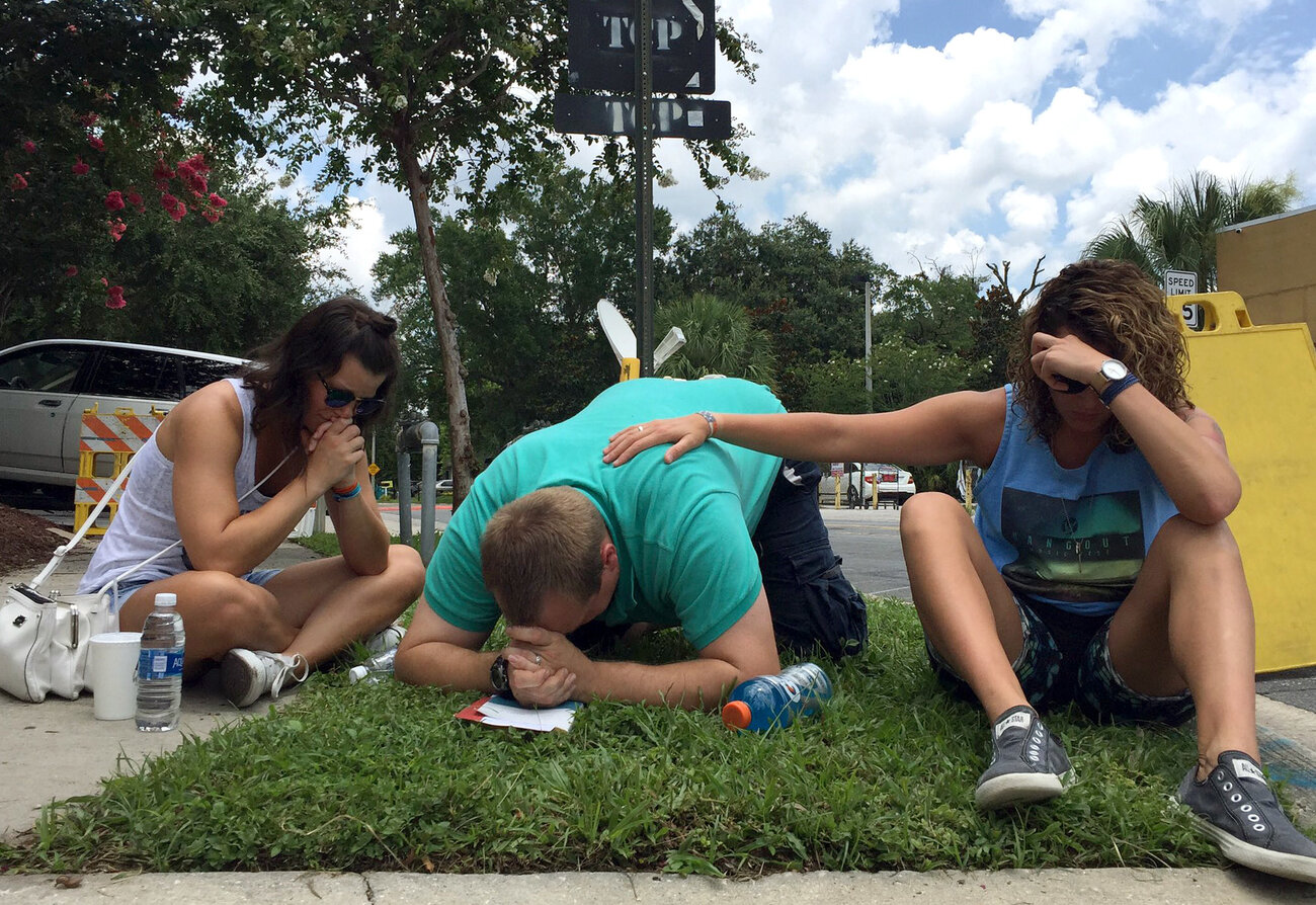 People pray on Orange Ave. in Orlando, near the Pulse night club.