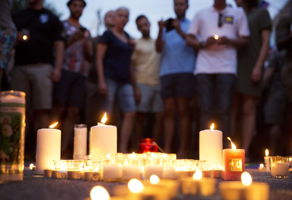 Mourners gather around candles lit during a vigil after the deadly shooting at the Pulse Orlando nightclub on Sunday. (David Goldman/AP)