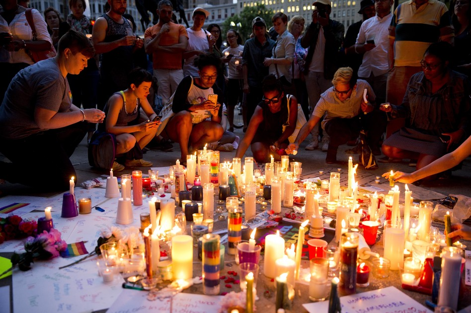 People gather Monday in Philadelphia for a vigil in memory of the victims of the Orlando, Fla., mass shooting. (Matt Rourke/AP)