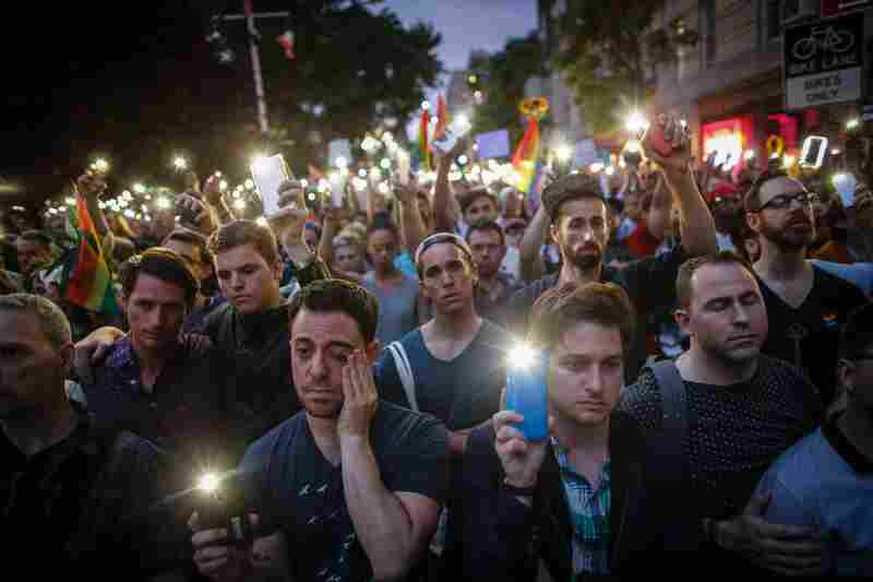 "People hold candles and lights during a vigil outside the Stonewall Inn. New York Gov. Andrew Cuomo joined the vigil and delivered a full-throated demand for what he called ""sensible gun control."""