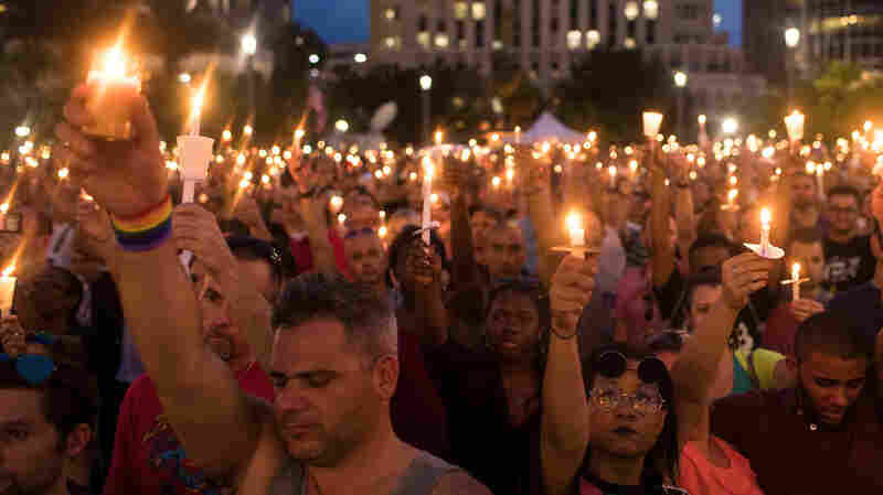 People hold candles during an evening memorial service in Orlando for the victims of the Pulse Nightclub shootings.