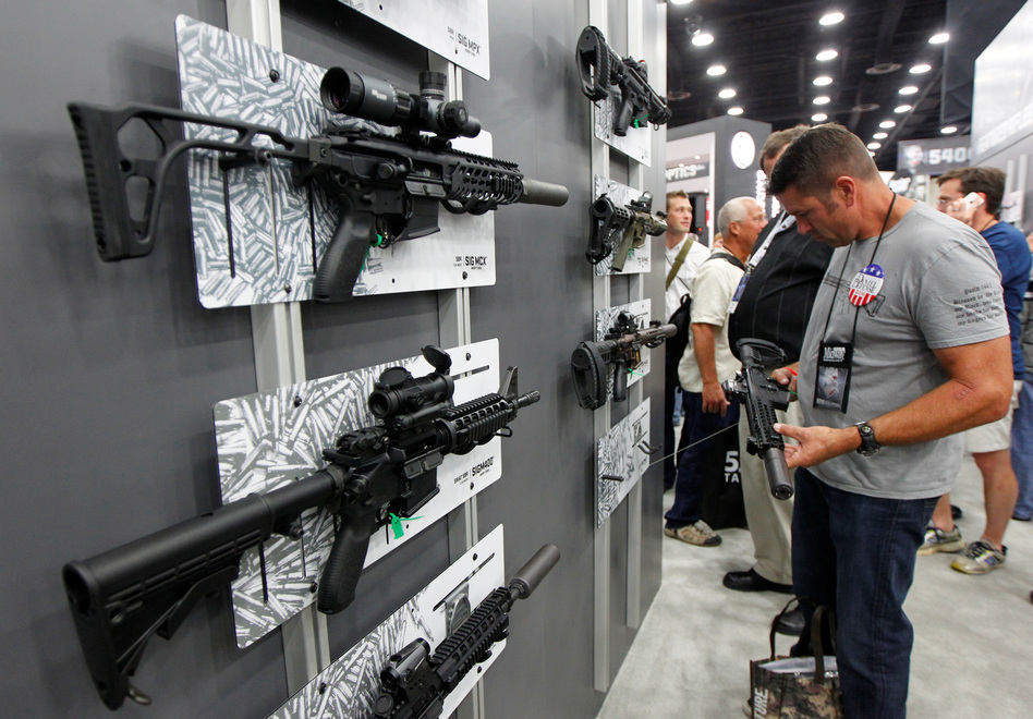 A Sig Sauer MCX rifle can be seen on display at the top left of this photo as NRA gun enthusiasts view the Sig Sauer display at the National Rifle Association's annual meetings & exhibits show in Louisville, Ky., in May. (John Sommers II/Reuters)