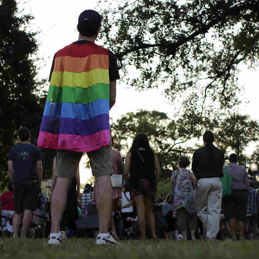 A man wears a rainbow cape during a memorial vigil for the victims of Orlando's Pulse nightclub shooting Thursday in San Antonio.