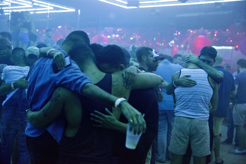 Club goers embrace at the approximate time one week ago that the Pulse nightclub mass shooting began. The music is turned off on the dance floor to observe a moment of silence at Parliament House, an LGBT nightclub early Sunday in Orlando, Fla. (David Goldman/AP)
